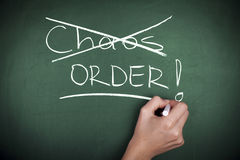 Chaos or Order. Hand crossed chaos and wrote order on chalkboard Stock Image