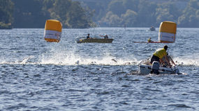 Chaos of swimming arms in the water and boats Stock Photos