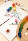 Chaos of tools and paint tubes on white canvas Royalty Free Stock Photography