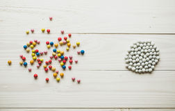 Chaotic colorful balls and organized white balls. Conceptual of Royalty Free Stock Images