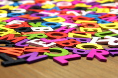 Chaotic English Wooden Multicolored Letters On The Brown Wood Ba. Random Chaotic Pattern From English Wooden Multicolored Letters On the Brown Wood Background Stock Images
