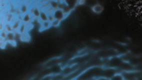 Chaotic gusts of wind and waves of black paint on a blue background. View from above stock footage