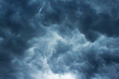 CHAOTIC STORM CLOUDS. Dark ominous cloud situated low in the sky with patch of light royalty free stock image