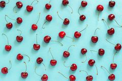Chaotically scattered red ripe sweet cherry on blue background, texture Top view, Flat lay stock images