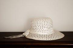 Chapéu à moda bonito do verão na tabela de madeira escura com fundo branco Sunhat da mulher elegante fotos de stock