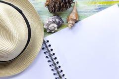 Chapéu, conchas do mar e caderno de palha em de madeira colorido com curso Imagens de Stock