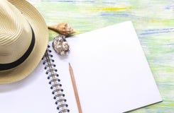 Chapéu, conchas do mar e caderno de palha na tabela de madeira colorida w Fotos de Stock Royalty Free