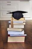 Chapéu da graduação em livros imagem de stock