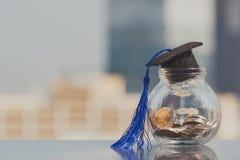 Chapéu da graduação no dinheiro das moedas na garrafa de vidro no fundo branco fotos de stock