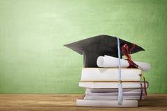 Chapéu da graduação, rolo do diploma e livros na tabela de madeira imagem de stock royalty free