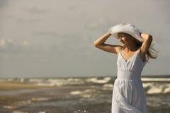 Chapéu da terra arrendada da menina na praia. fotografia de stock