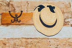 Chapéu das senhoras que pendura no gancho na casa velha da exploração agrícola Fotos de Stock
