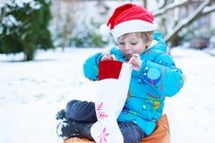 Chapéu de espera de Santa do Natal do menino pequeno feliz da criança Imagem de Stock Royalty Free
