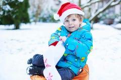 Chapéu de espera de Santa do Natal do menino pequeno feliz da criança Imagem de Stock