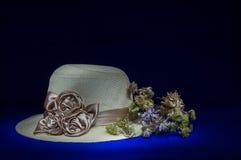 Chapéu de palha com as flores na vida preta do fundo-ainda Foto de Stock Royalty Free