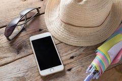 Chapéu de palha com saco, telefone, óculos de sol e guarda-chuva da palha na madeira Fotos de Stock