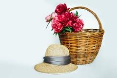 Chap?u de palha com um ramalhete de pe?nias cor-de-rosa luxuosos fotos de stock