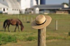 Chapéu de palha de Amish com a exploração agrícola no fundo imagem de stock
