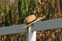 Chapéu de palha de Amish que coloca sobre o cargo da cerca com campo de milho nos vagabundos fotografia de stock