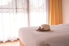 Chapéu de palha na cama branca Imagem de Stock