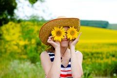 Chapéu de palha vestindo da jovem mulher com dois girassóis Imagens de Stock