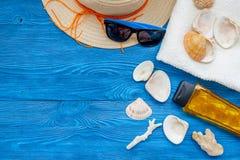 Chapéu de palha, vidros de sol, escudos e creme do sunblock para férias do mar no espaço de madeira azul da cópia da opinião supe foto de stock