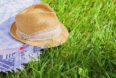 Chapéu de palha de vime do verão do vintage com fita colorida e lenço no gramado no parque fotos de stock royalty free