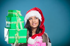 Chapéu de Papai Noel da raça misturada da menina com caixas de presente Fotografia de Stock