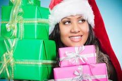 Chapéu de Papai Noel da raça misturada da menina com caixas de presente Imagem de Stock Royalty Free