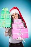 Chapéu de Papai Noel da raça misturada da menina com caixas de presente Imagem de Stock