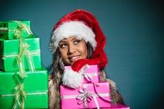 Chapéu de Papai Noel da raça misturada da menina com caixas de presente Foto de Stock