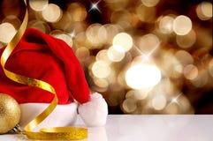 Chapéu de Santa Claus com fundo dourado dourado da bola e da fita Fotografia de Stock