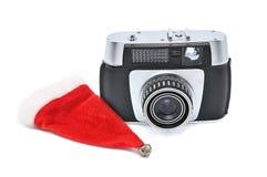 Chapéu de Santa Claus e câmera do vintage para fotografar em um fundo branco foto de stock royalty free