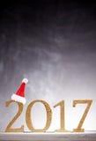 Chapéu de Santa na decoração dourada do ano novo em 2017 Imagens de Stock