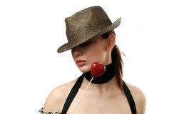 Chapéu desgastando da mulher que mostra o bolinho dado forma coração Imagem de Stock Royalty Free