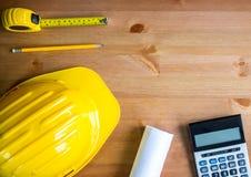 Chapéu do desenhista, lápis, fita métrica, modelo, calculadora, tampo da mesa da madeira, vista superior, espaço da cópia imagem de stock