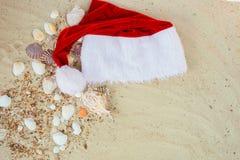 Chapéu do Natal na praia Santa a areia perto dos shell feriado Férias do ano novo Copie o espaço Quadro Vista superior Imagem de Stock Royalty Free