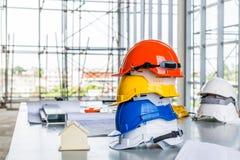 Chapéu duro branco, alaranjado, amarelo e azul do capacete de segurança com const imagem de stock