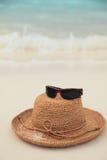Chapéu e óculos de sol de palha no console tropical Fotos de Stock Royalty Free