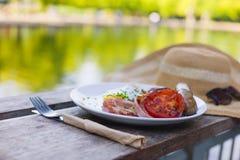 Chapéu e café da manhã por uma lagoa no parque Imagens de Stock