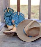 Chapéu e carregadores de cowboy que inclinam-se de encontro a uns trilhos Imagem de Stock Royalty Free