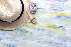 Chapéu e conchas do mar de palha em de madeira colorido com curso ou vacati Imagem de Stock