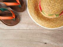 Chapéu e deslizadores de palha na tabela de madeira Vista superior Vacatio do verão fotografia de stock