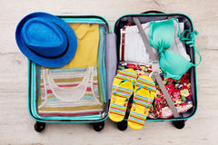 Chapéu e deslizadores na mala de viagem embalada foto de stock royalty free