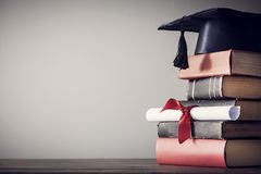 Chapéu e diploma da graduação com o livro na tabela Fotografia de Stock