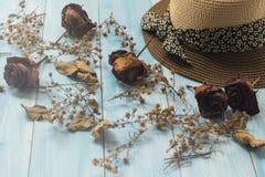Chapéu e flor seca no fundo de madeira Fotografia de Stock Royalty Free