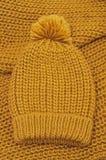 Chapéu e lenço feitos malha mostarda de lãs Foto de Stock