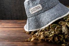 Chapéu e vassoura da sauna no fundo de madeira escuro foto de stock