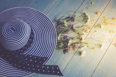 Chapéu fêmea, listrado, ramalhete dos wildflowers, vista superior Em um fundo de madeira Cor azul Imagem conceptual Foto de Stock