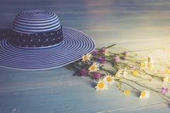 Chapéu fêmea, listrado, ramalhete dos wildflowers, vista superior Em um fundo de madeira Imagem conceptual Imagem de Stock Royalty Free